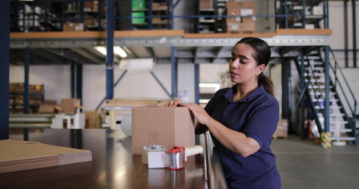 Female working in packing warehouse Live Action