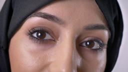 Eyes of young serious muslim girl in hijab is watching at camera, grey Archivo