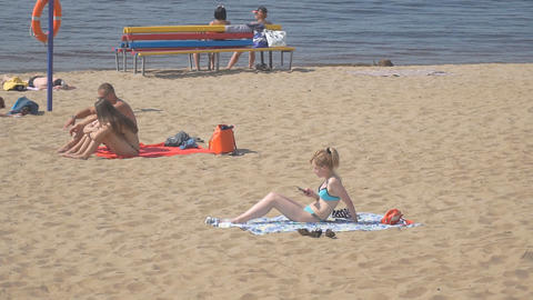 A young woman uses the cellphone resting on the beach Footage