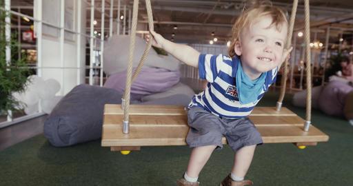 Little cute boy having fun on swings Footage