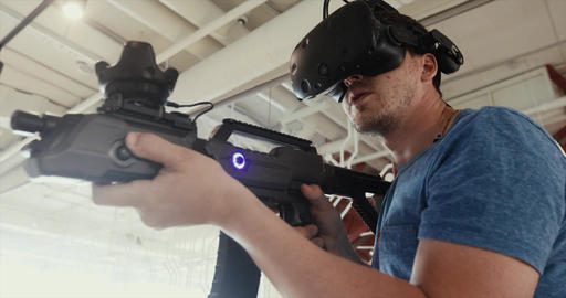 Guy playing VR sniper game with gun and glasses Footage