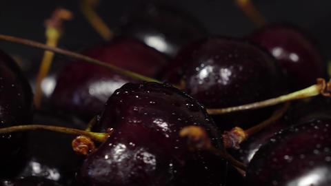 Cherry. Ripe cherries rotating over black background. Rotating Black Ripe Sweet Footage