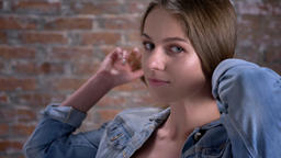 Young cute woman is watching at camera, touching hair, brick background, flirt Archivo