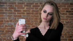 Young charming girl with smoky eyes make seifie on her smartphone, winking Footage