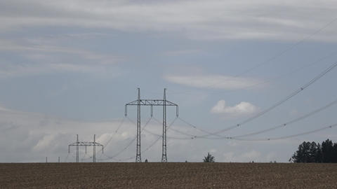 Large view on the powerlines on the field. High voltage post or high voltage Live Action