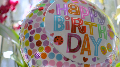 Close-up of Happy Birthday balloon quickly moving rotating reflecting light ビデオ