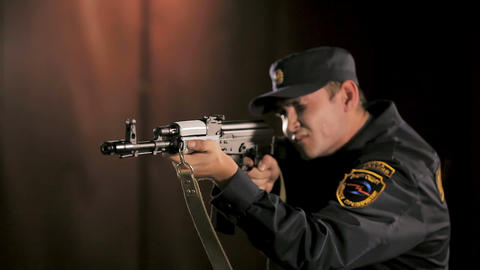 security man trains to fire automatic rifle in shooting gallery ビデオ