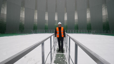 worker stands on metal bridge inside cooling tower GIF