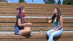 two girl friends talking to each other sitting on a bench in the park. slow Footage
