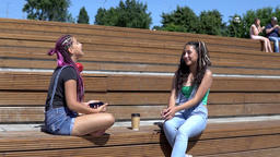 two girl friends talking to each other having a good mood sitting on a bench in Archivo