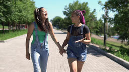 Two girls girlfriends are happy and jumping in the park in sunny weather. slow Footage