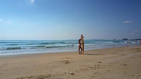 girl poses holding surfboard standing on seashore against horizon Footage