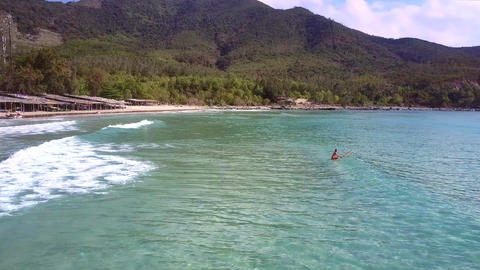 woman surfs floating on board in sea against tropical nature GIF