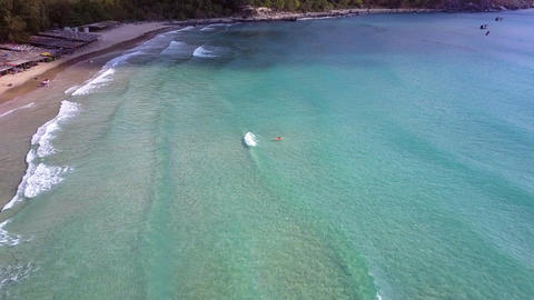 woman floats in ocean catching waves against coast ビデオ