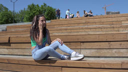 Girl talking on mobile phone sitting on bench in park. 4K Footage