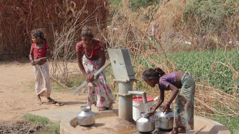 Indian rural girls pour water from the pump to the jugs.Rajasthan.Maunt-Abu.2016 Footage