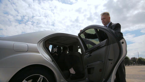bodyguard opens car door and goes with protected person to office GIF