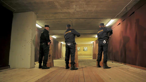 security men take pistols out of pockets to fire in shooting gallery Archivo
