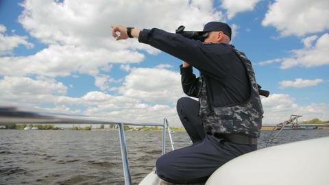 water policeman sits on motorboat monitoring river through binoculars Live Action