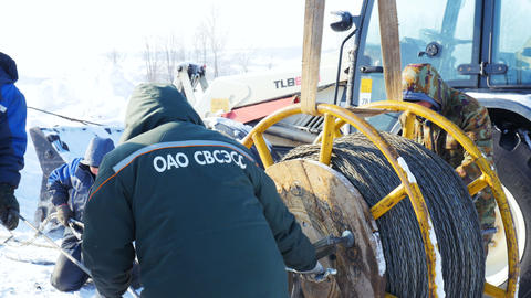 workers fasten steel wire rope coil near tractor in winter Footage