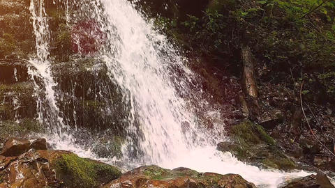 Slow motion of a small mountain waterfall. 240fps. The mountain stream falls Footage