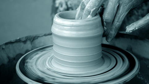 Workshop molding of clay on potter's wheel. Dirty hands in the clay Footage