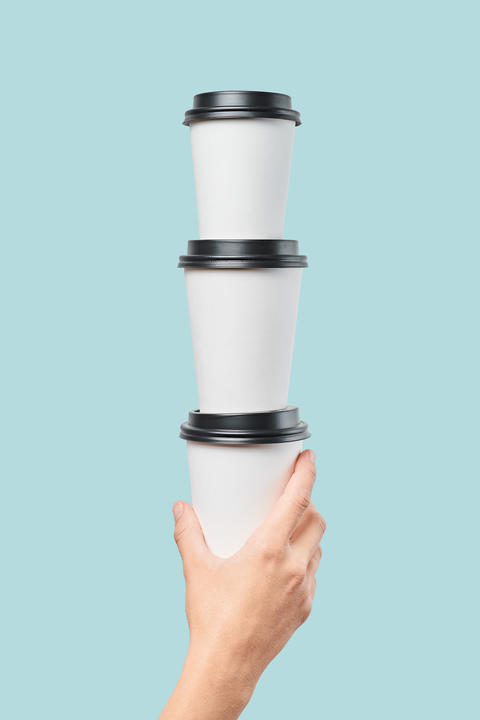 Crop hand holding stack of paper cups フォト