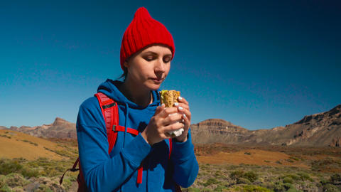 Hiking woman eating sandwich after hike on Teide, Tenerife. Caucasian female Live Action