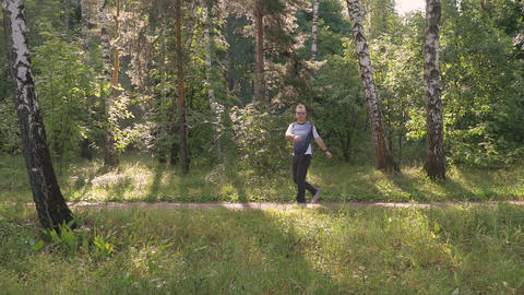 A man is running in the park on a summer day. He trains and performs exercises Footage