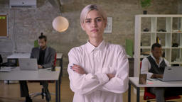 Young pretty businesswoman is standing and crossing her arms in office Footage