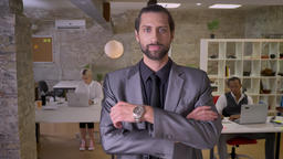 Businessman with beard is standing with arms crossed and watching at camera in Footage