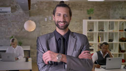 Happy businessman with beard is standing with arms crossed and watching at Footage