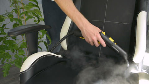 Hand is cleaning office chair with a steam cleaner. Home cleaning concept Live Action