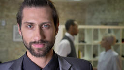 Handsome confident businessman with beard is watching at camera in office Footage