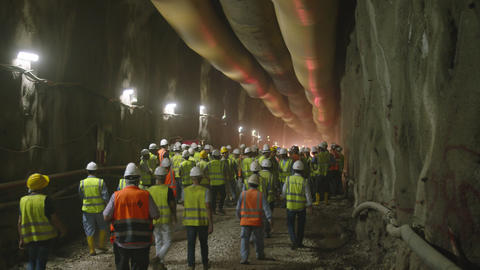 Construction workers walking into a large tunnel Footage
