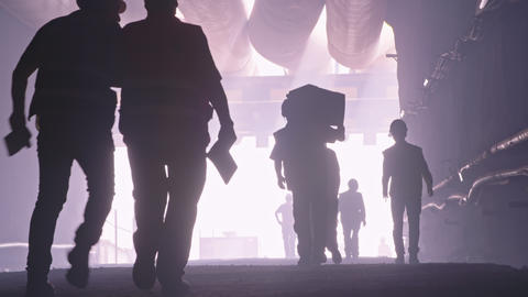 silhouette of many construction workers walking out from a large tunnel Footage