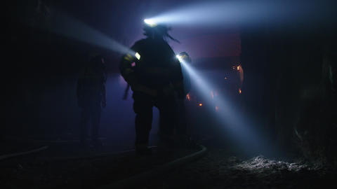 Firefighters during a rescue operation in a dark tunnel filled with smoke Footage