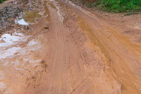 Mud and puddles on the dirt road in countryside フォト