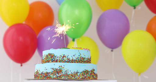 Blue Birthday cake with sparkler and colorful balloons Live Action