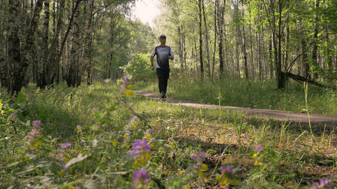 A middle-aged man, doing sports. He goes for a walk in the woods. Leads a GIF
