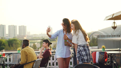 Cheerful female friends are taking selfie with smartphone and laughing standing Footage