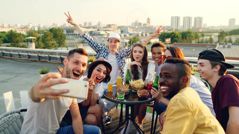 Happy young men and women are taking selfie with smart phone posing, laughing ビデオ