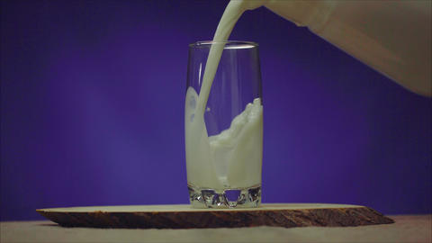 Milk from a jug into a glass. A glass with milk on a blue background. Milk from Archivo