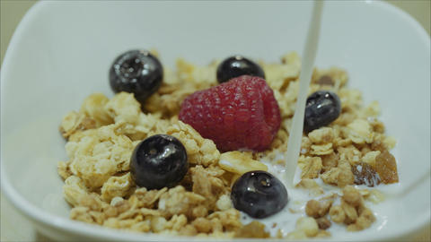 Berries, flakes, pour milk. Raspberry with milk. Raspberry in milk. Berries and Live Action