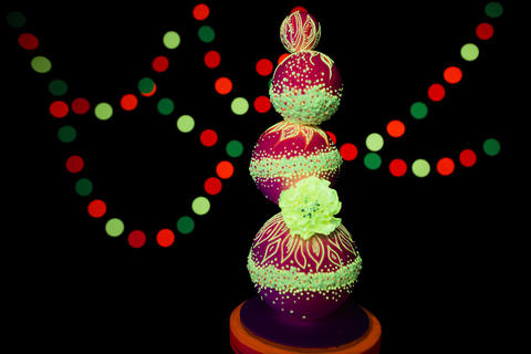 Neon UV photography bright colorful wedding cake glows fluorescent colors on a Photo