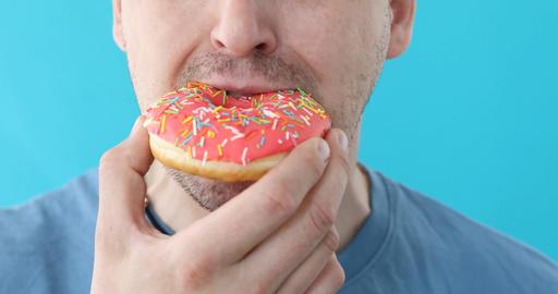 Man eat donut closeup on a blue background フォト