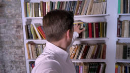 Young boy puts book on shelf, find dollar, put it in pocket, stealing concept Footage