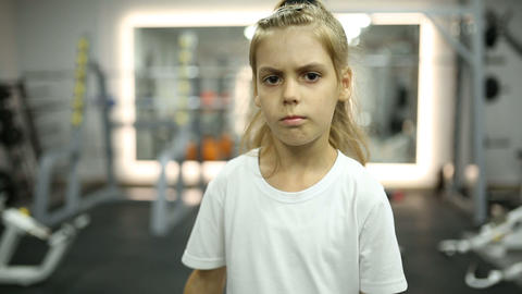A little girl is lifting dumbbells in a gym Footage