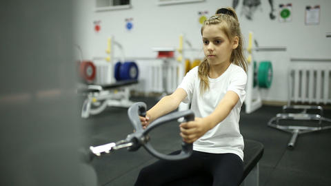 A little girl in the gym is exercising on the machine 영상물