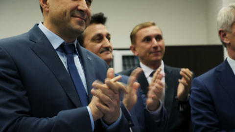 joyful businessmen applaud to speaker in hall GIF